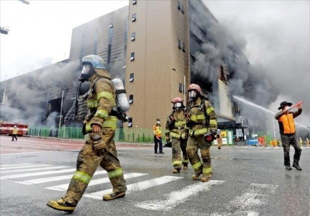 """< """"진입 못 해""""…안타까운 발걸음 > 경기 이천시 마장면 쿠팡 덕평물류센터 화재가 이틀째 이어진 18일 소방대원들이 화재 진압작업에서 철수하고 있다. 화재 현장에선 검은 연기가 하루 종일 치솟아 올랐다. 이천=신경훈 기자"""