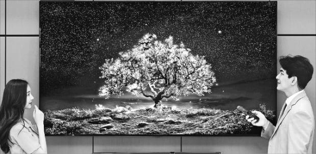 LG전자 모델들이 4K 올레드 TV 중 세계 최대 크기인 83인치 제품을 작동해 보고 있다.  LG전자 제공