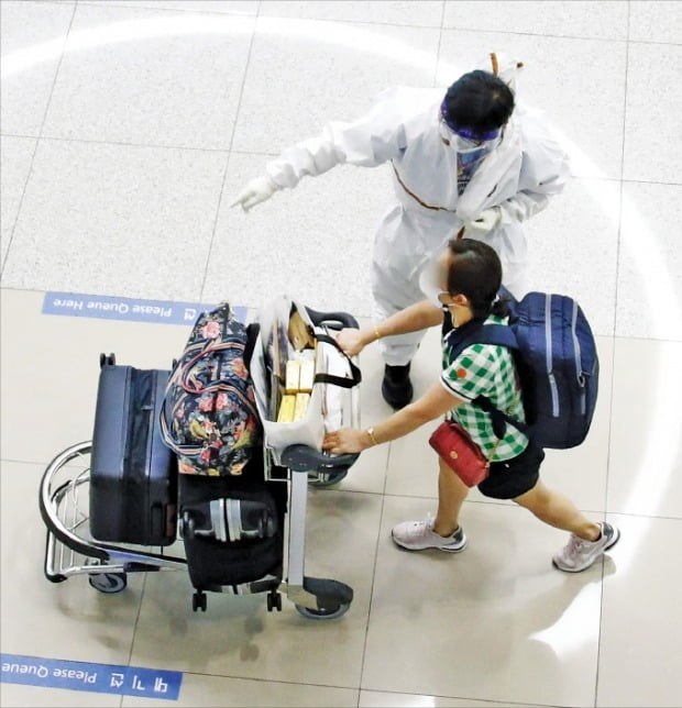 기존 코로나19 바이러스보다 강한 전파력을 지닌 '델타 플러스 변이'가 확산하면서 세계 각국이 방역을 강화하고 있다. 25일 인천국제공항에서 해외 입국자가 직원의 안내를 받고 있다.  /뉴스1