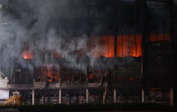 18일 오후 경기도 이천시 마장면 쿠팡 덕평물류센터 화재 현장 지상층 내부에 날이 어두워지면서 불길이 보이고 있다./ 사진=연합뉴스