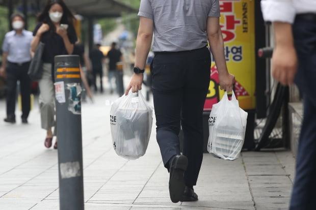 수도권의 '사회적 거리두기'가 4단계로 격상된 지 1주일이 된 19일 점심시간 서울 종로구 관철동 젊음의거리 일대 식당가에서 직장인이 도시락을 찾아가고 있다. 사진=연합뉴스