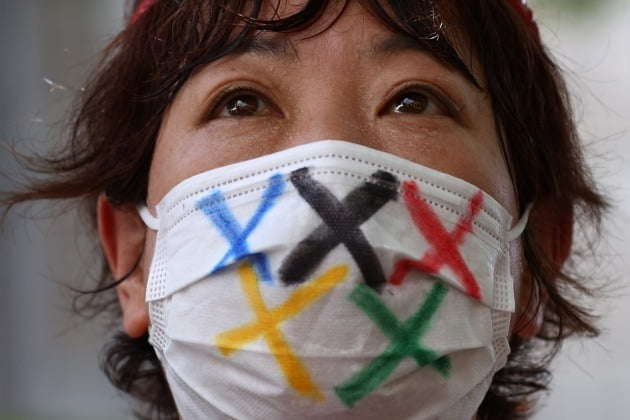 일본 도쿄 신주쿠에서  한 여성이 도쿄올림픽 반대 시위를 하는 모습/사진=로이터