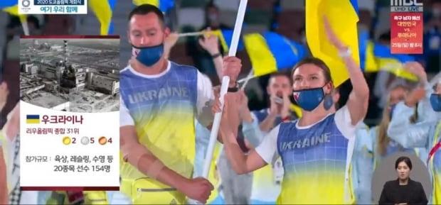 우크라이나 선수단이 입장하자 체르노빌 폭발 사진을 띄운 MBC 화면. 사진=MBC 갈무리