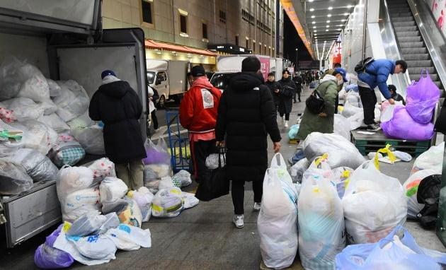△동대문 패션도매상가 앞에서 구매 대행을 하고 짐을 나르는 사입 삼촌들이 작업을 하고 있다