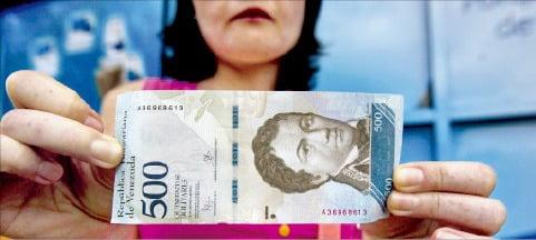 베네수엘라의 한 국민이 볼리바르 지폐를 들어 보이고 있다. 물가 급등 영향으로 이 화폐 가치는 계속 떨어지고 있다. /한경DB