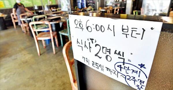 서울 마포구의 한 식당 입구에 거리두기 2주 연장을 알리는 문구가 적혀 있다. 23일 정부는 수도권 거리두기 4단계 조치를 2주간 더 연장했다.  /김범준 기자