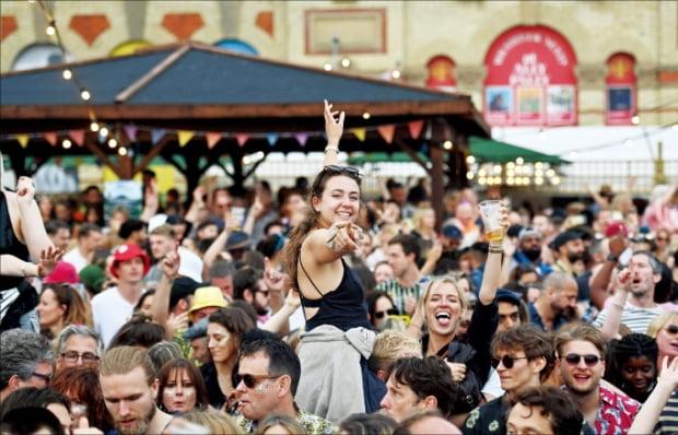 영국 런던의 알렉산드라 팰리스 공원에서 열린 칼레이도스코프 축제 참가자들이 맥주를 마시면서 환호하고 있다. 지난 24일 진행된 이 축제는 봉쇄 조치가 끝난 뒤 열린 첫 대형 행사다.  AFP연합뉴스