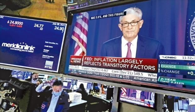 지난 28일 제롬 파월 미국 중앙은행(Fed) 의장이 성명을 발표하는 모니터 화면 뒤로 뉴욕증권거래소(NYSE) 직원들이 증권 중개 업무를 보고 있다. Fed는 이날 연방공개시장위원회(FOMC)를 열어 기준금리를 종전의 연 0.00~0.25%로 동결했다. 테이퍼링(자산 매입 축소)에 대해서는 구체적인 일정을 밝히지 않았다. /로이터연합뉴스