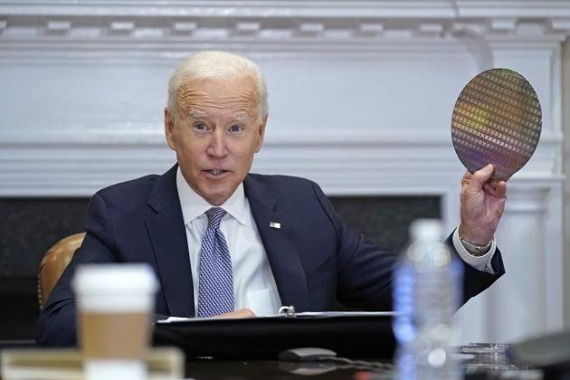 조 바이든 미국 대통령이 4월 12일 삼성전자, 인텔 등을 초청해 연 '반도체 CEO 화상회의'에서 실리콘 웨이퍼를 흔들며 반도체 공급 확대를 위한 투자를 당부하는 모습  /AP·연합뉴스