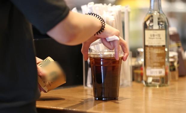 서울 성동구의 한 프랜차이즈형 커피전문점을 찾은 시민이 포장주문한 커피를 받고 있다. /사진=연합뉴스
