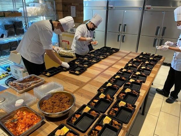 일본 도쿄올림픽에 출전한 한국 선수단을 지원하는 대한체육회의 현지 급식지원센터에서 20일 조리사들이 음식을 도시락 용기에 담고 있다. 사진=연합뉴스