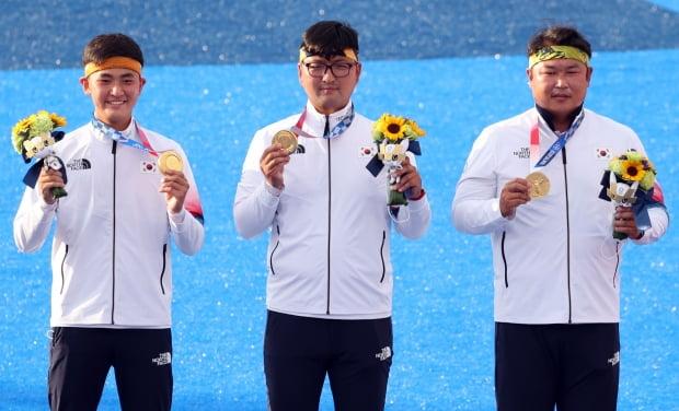 26일 일본 유메노시마 공원 양궁장에서 열린 도쿄올림픽 남자 단체전 시상식에서 한국 김제덕(왼쪽부터), 김우진, 오진혁이 금메달을 목에 걸고 기념촬영을 하고 있다/사진=연합뉴스