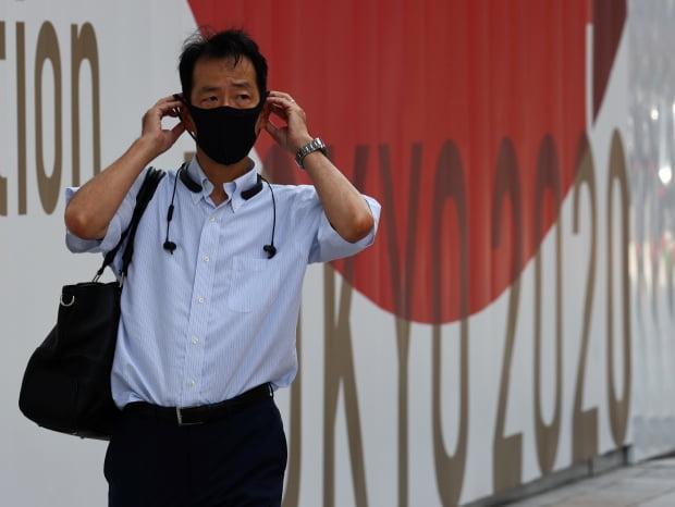 마스크를 쓴 남성이 도쿄올림픽 안내판 앞을 지나고 있다. 사진=REUTERS