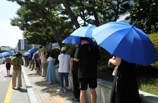 29일 광주 광산구 선별진료소에서 시민들이 구청에서 제공한 우산으로 햇볕을 가리고 줄 서 있다. /사진=연합뉴스