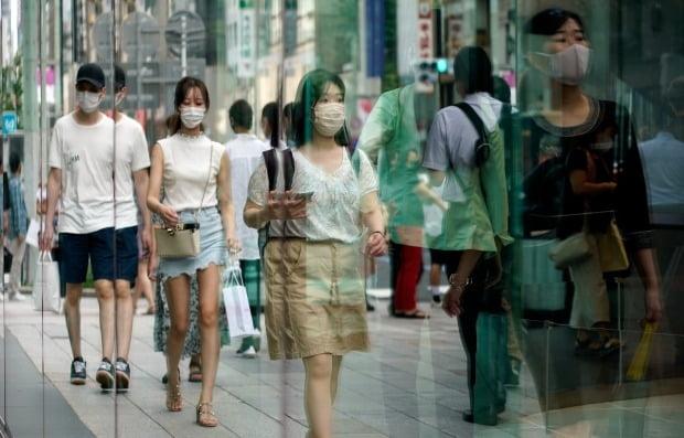 일본 도쿄 긴자 쇼핑가의 유리창에 마스크를 쓴 행인들이 반사되고 있다. 사진=EPA