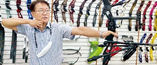 박경래 윈엔윈 대표가 위아위스 활시위를 당기며 제품의 특징을 소개하고 있다. 작은 사진은 도쿄올림픽에서 '위아위스' 활을 사용한 안산.   김동현 기자