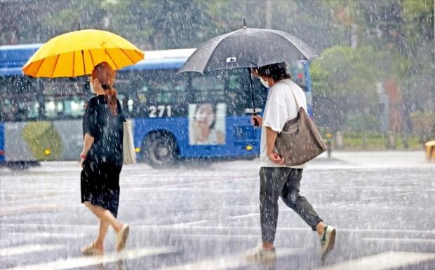 < 이번주 우산 챙기세요 > 1일 폭염 속에 소나기가 쏟아지자 서울 종로구에서 시민들이 우산을 쓴 채 발걸음을 옮기고 있다. 기상청은 이번주 내내 전국적으로 비가 이어질 것으로 예보했다.  연합뉴스