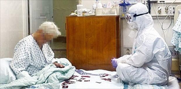 < 의료진의 헌신…방호복 입고 93세 할머니와 화투 > 삼육서울병원 음압병동에서 방호복을 입은 간호사 이수련 씨(29)가 코로나19에 확진돼 홀로 격리된 할머니 환자(93)를 위해 화투 '그림 맞추기 치료'를 하고 있다. 이 사진은 지난해 8월 찍힌 것으로 최근 온라인에 공개돼 큰 화제를 모았다. 이 병원의 간호사들은 중증 치매를 앓는 할머니를 위해 먼저 그림 치료를 제안했다.  대한간호협회 제공