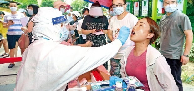 < '코로나 진앙지' 우한서 15개월 만에 확진자 > 2019년 말 세계 최초로 코로나19 사례가 보고된 중국 후베이성 우한에서 주민 1100만여 명을 대상으로 지난 3일 코로나19 전수조사를 시작했다. 전날 우한에서 15개월 만에 확진자가 다시 나온 데 따른 조치다. 방역복을 입은 의료진이 한 여성의 검체를 채취하고 있다. /EPA연합뉴스