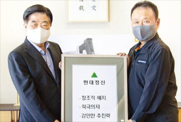 20일 두산인프라코어 인천 공장을 방문한 권오갑 현대중공업지주 회장(왼쪽)이 손동연 사장에게 '현대정신' 액자를 전달하고 있다.  /현대중공업 제공