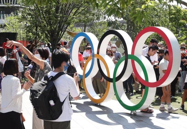 도쿄올림픽 개막일인 23일 일본 도쿄 신주쿠(新宿) 국립경기장에서 앞 광장에서 일본 시민들이 오륜기 조형물을 배경으로 사진 찍고 있다. /사진=연합뉴스