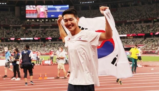 1일 도쿄올림픽 남자 높이뛰기에서 2m 35 한국신기록을 세우며 4위를 차지한 우상혁이 도쿄 올림픽스타디움에서 경기 종료 후 태극기를 펼치며 기뻐하고 있다. 사진=연합뉴스