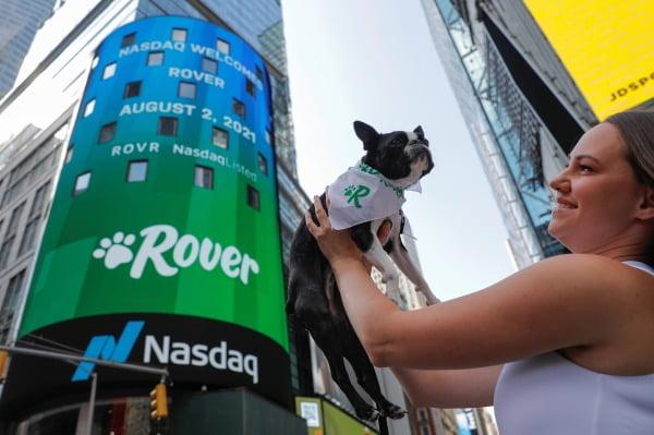 반려동물 돌봄서비스를 제공하는 미국 로버의 한 직원이 지난 2일 뉴욕 나스닥 빌딩 앞에서 포즈를 취하고 있다. 로버는 같은 날 나스닥에 상장했다. 로이터연합뉴스