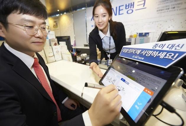 IBK기업은행은 영업점을 방문한 고객이 종이를 대체한 태블릿PC를 활용해 전자신청서를 작성하는 'IBK전자문서시스템'을 전 영업점에서 시행하고 있다. /IBK기업은행