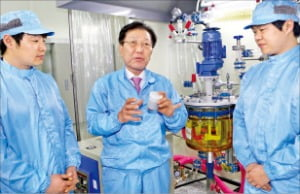 이준호 덕산그룹 회장(가운데)이 덕산하이메탈 본사 공장에서 연구원들과 이야기하고 있다.  덕산하이메탈  제공