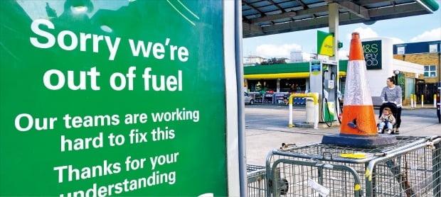 < 브렉시트 여파…영국 주유소 '기름 대란' > 국제 유가가 고공행진하고 있다. 서부텍사스원유(WTI) 가격은 3년 만에 최고치로 치솟았고 브렌트유는 28일 한때 심리적 마지노선으로 꼽히는 배럴당 80달러를 넘어섰다. 공급난에 허덕이는 영국에선 브렉시트 이후 인력난까지 가중되면서 상당수 유조차가 운행을 멈췄다. 27일(현지시간) 영국 런던의 한 주유소에 기름이 떨어졌다는 안내문이 붙어 있다.  로이터연합뉴스