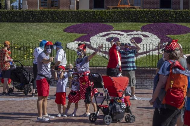 (사진) 미국 캘리포니아주 애너하임의 '디즈니랜드'가 지난해 4월 30일 코로나19로 폐쇄된 이후 1년 만에 개장한 가운데 입장객들이 기념촬영하고 있다. /AFP 연합뉴스