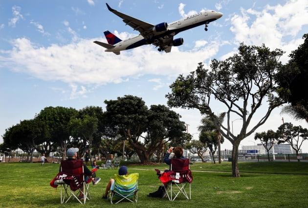 (사진) 로스앤젤레스 국제공항 옆 공원에 둘러앉은 한 가족이 델타항공 여객기가 이륙하는 것을 지켜보고 있다. /AFP 연합뉴스