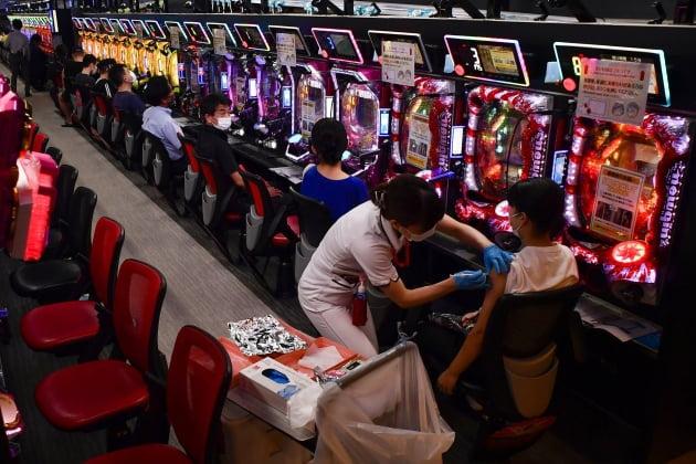 (사진) 한 여성이 9월 13일 일본 오사카의 파칭코 업소에서 모더나 백신 1차 접종을 하고 있다. 인근 병원은 코로나19 백신 임시 접종소가 된 이 업소에 의료진을 파견해 이틀 동안 직원과 단골손님 등 1500여 명에게 백신을 투여했다. /AP 연합뉴스