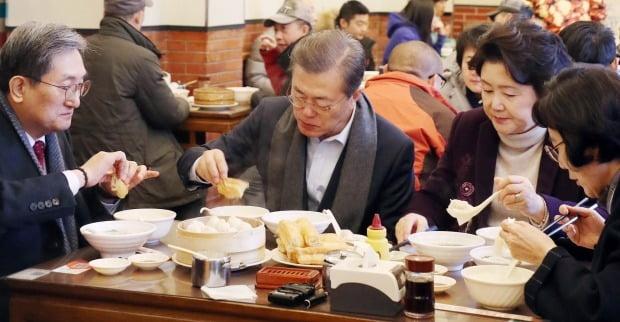 문재인 대통령과 부인 김정숙 여사가 2017년 12월 14일 오전 중국 베이징 조어대 인근 한 현지 식당에서 중국인들이 즐겨 먹는 아침 메뉴인 만두(샤오롱바오), 만둣국(훈둔), 꽈배기(요우티아오), 두유(도우지앙)을 주문해 식사를 하고 있다. 문 대통령은 당시 혼밥, 외교적 홀대 논란에 휘말렸다. 사진=연합뉴스