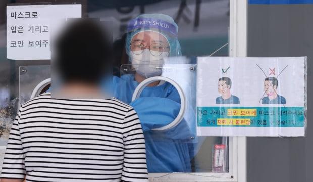 19일 오전 서울역 중구 신종 코로나바이러스 감염증(코로나19) 임시선별검사소에서 의료진이 검체 채취를 하고 있다. 사진=연합뉴스