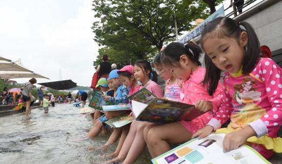 어린이들이 26일 서울 송파구 성내천물놀이장에서 책을 읽고 있다. 성내천물놀이장 도서관은 오는 8월3일까지 운영된다. 신경훈 기자 khshin@hankyung.com