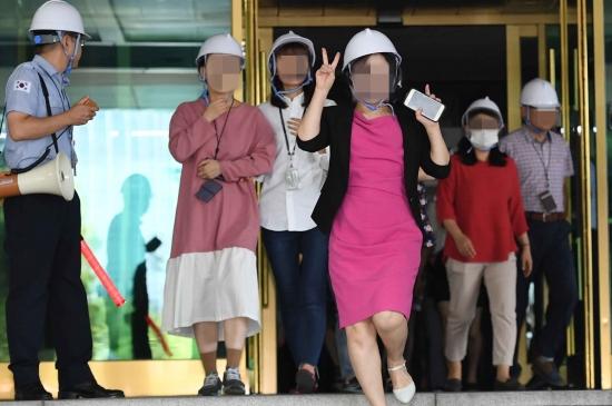 12일 오후 종로구 정부서울청사에서 열린 '지진대피훈련'에서 한 공무원이 청사 건물 밖으로 대피하며 손으로 '브이' 포즈를 취하고 있다. 이번 훈련은 '2018 지진 안전 주간(9월 10~14일)'을 맞아 실시됐다./김범준기자bjk07@hankyung.com